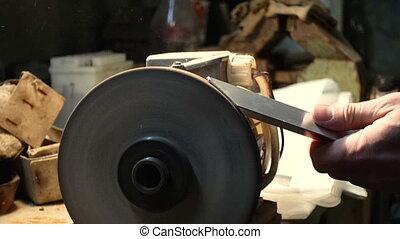 Worker man with grinding machine in workshop