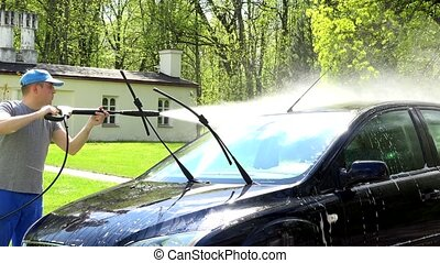 Worker man with high pressure water jet tool washing his car automobile.
