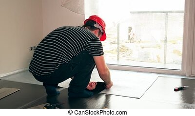 Worker man with scissors cutting teflon underlay mat on floor