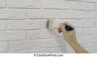worker manually varnishes decorative brick on the wall....