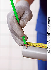 Worker marking a measurement on a tube