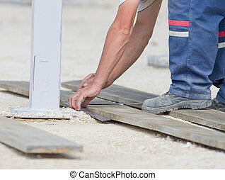 Worker marking plank for cutting
