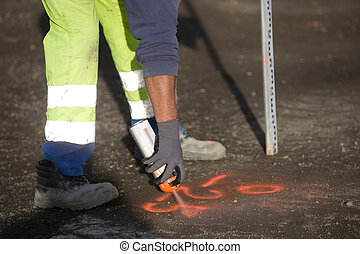 Worker marks a spot on asphalt with florescent spray paint...