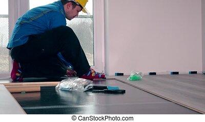 worker master in blue work wear install the laminate floor....