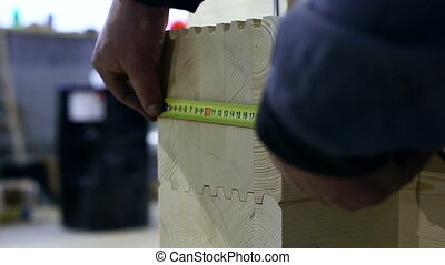 Worker measures height of profiled bar, close-up - View on...