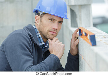 worker measures the curvature of the wall with a level