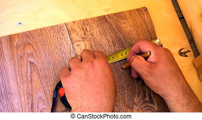worker measures with tape measure linoleum.