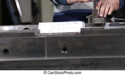 Worker measuring caliper