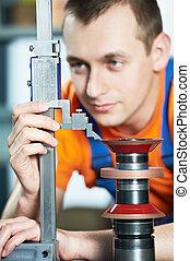 mechanical technician measuring diamond cutting tool machine center at tool workshop