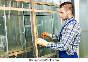 Worker measuring glass at factory