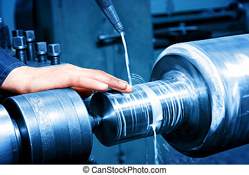 Worker measuring on industrial turning machine. Industry