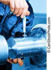 Worker measuring on industrial turning machine. Industry -...