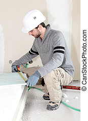 Worker measuring plasterboard