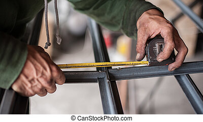 Worker measuring steel with measuring tape