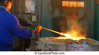 Worker melting metal in furnace at workshop 4k