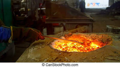 Worker melting molten in furnace at foundry workshop 4k