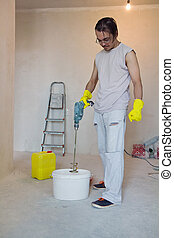 Worker mixing glue with a power drill