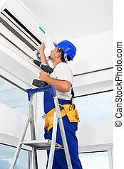 Worker mounting air conditioning unit - Worker finished ...