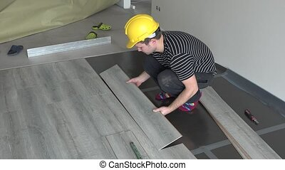 Worker mounting down laminate wood flooring boards together with great care