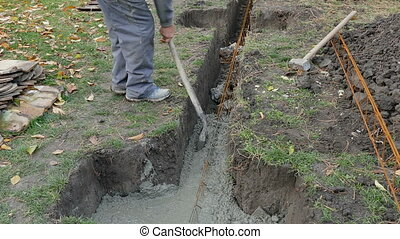 Worker moving concrete in a foundation trench using shovel...