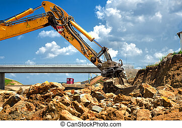 worker moving rocks with excavator on construction site