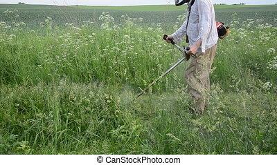 worker mow wet grass - worker gardener man mowing trimming...