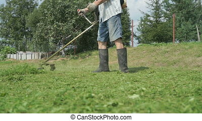 Worker mowing a grass using trimmer outdoors in sunny day