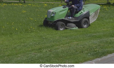 Worker mows green grass lawnmower on spring day. UltraHD...
