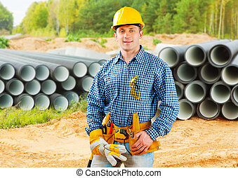 worker near stack of big pipes