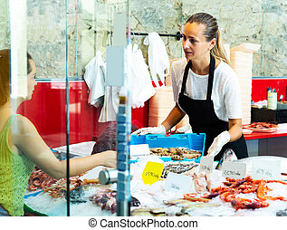 Polite female worker of fish shop offering fresh raw langoustines to woman customer