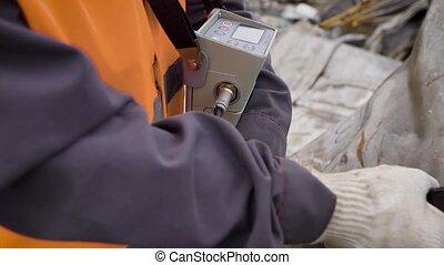 worker of scrap metal processing plant is exploring big...