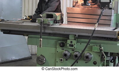 Worker on a machine metal lathe in factory. Machining process in the factory