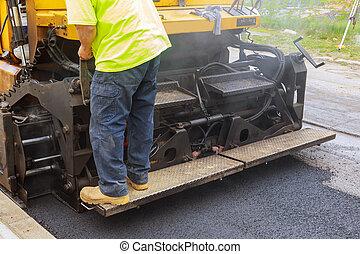 Worker on Asphalting paver machine during Road street repairing works Asphalting and Repair of roads