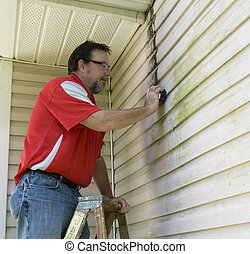 Worker On Ladder Cleaning Algae And Mold From Vinyl Siding