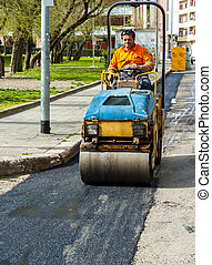 Worker on light vibration roller compactor at asphalt pavement works for road repairing