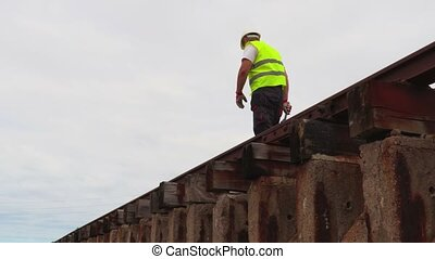 Worker on railway in rainy day