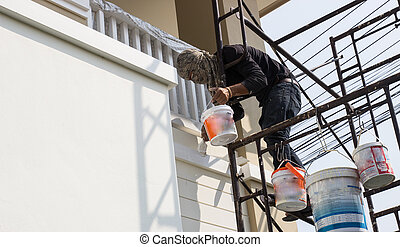 worker on scaffold holding brush painting wall