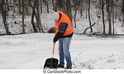 Worker on sidewalk with back pain in winter