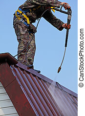 Worker on top of roof, with high pressure washer, cleans...