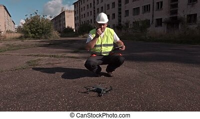 Worker on walkie talkie and tablet PC near drone