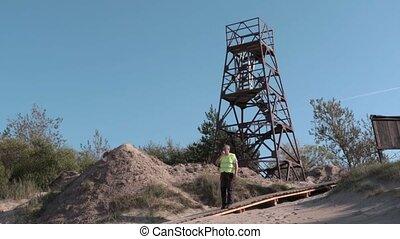 Worker on walkie talkie at the metal tower