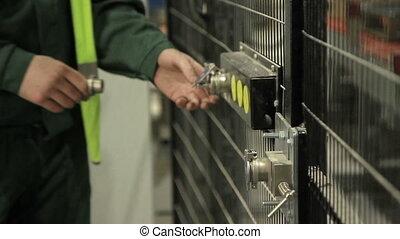 Worker opening security door in factory