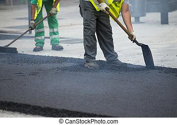 Worker operating asphalt paver machine during road ...