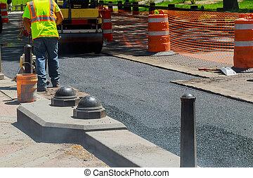 Worker operating asphalt paver machine during road construction repairing works