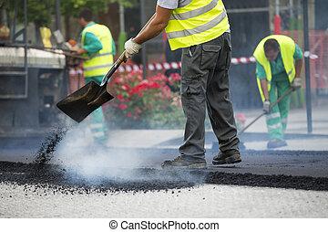 Worker operating asphalt paver machine during road...