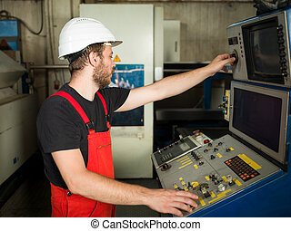 worker operating control panel in industrial setting