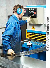 worker operating guillotine shears machine - worker at...