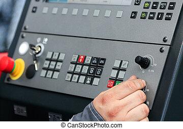 operating the controls of CNC machine
