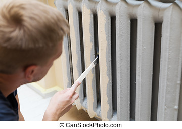 worker painting a heating radiator with paint brush