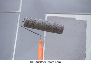 painting a wall with painting roller